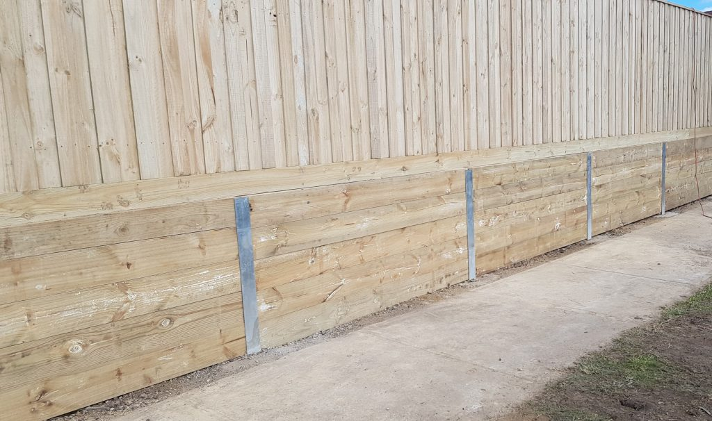 Timber sleeper retaining wall with timber pailing fence
