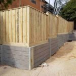 concrete retaining wall with wood fence on top