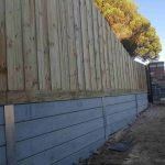 concrete wall with timber fence above