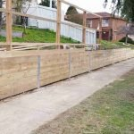 front yard perimeter wood retaining wall with fence above being built