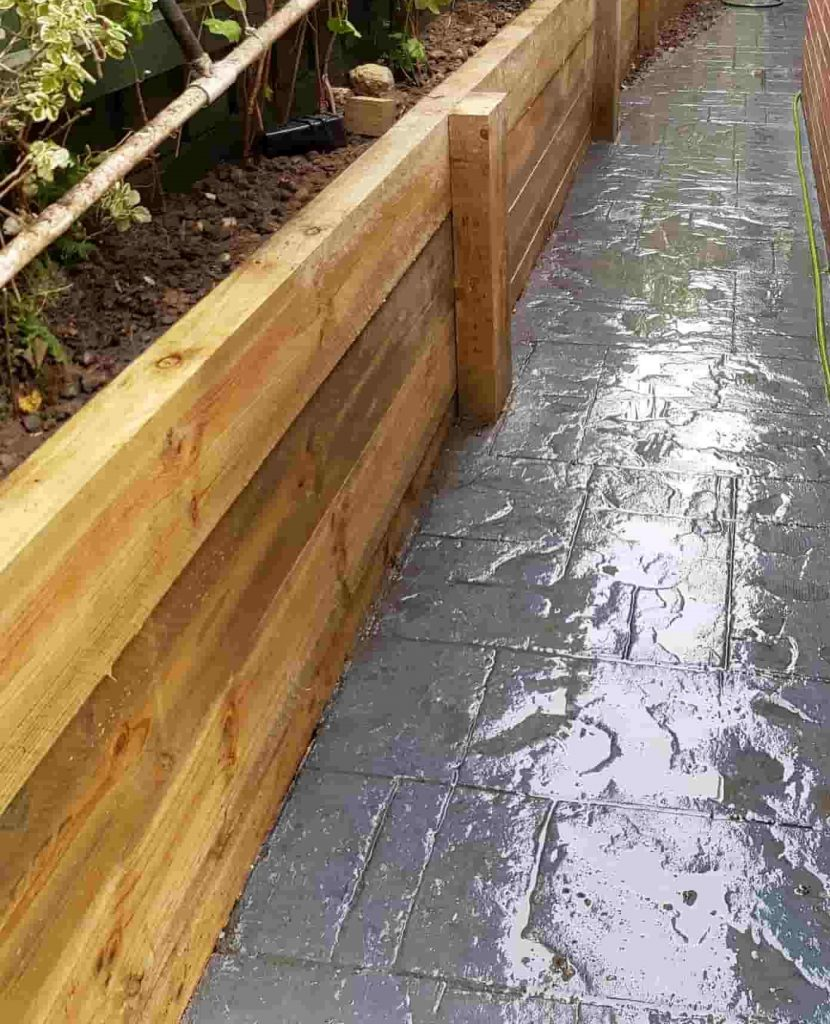 short timber sleeper retaining wall with timber posts for garden bed